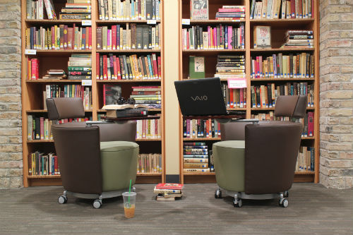 two workstations in front of bookcases at the library