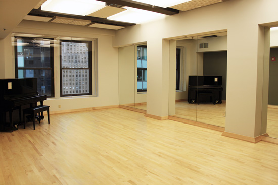 Studio B has an upright piano, wood floor, and mirrors.